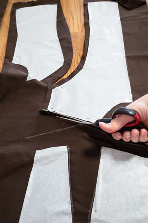 woman's hand cuts brown fabric by scissors according with pattern layouts of dress on wooden table at home Archivio Fotografico