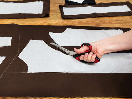 hand cuts brown fabric by scissors according with pattern layouts of dress on wooden table at home