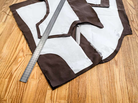 steel rule lays on a layout of sewing patterns of dress on brown fabric on wooden table at home