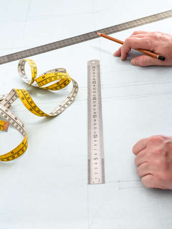 tailor's hands, measuring tape, rulers and pencil on pattern layout of dress drawn on graph paper at home