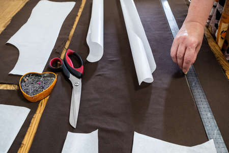 tailor draws pattern of dress on brown fabric with rule by soap at home Archivio Fotografico