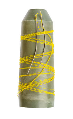 plastic bobbin with last yellow thread and two sewing needles cutout on white background