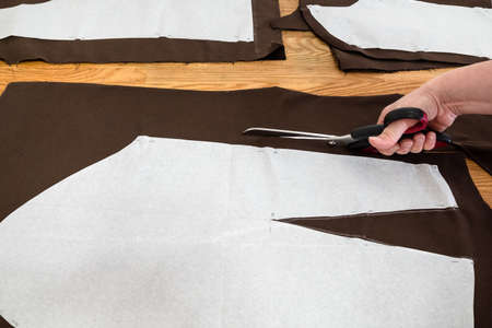 woman's hand cuts brown fabric by scissors according with layouts of sewing patterns of dress on wooden table at home Archivio Fotografico