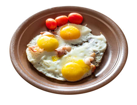 three fried eggs with bacon on brown ceramic plate cut out on white background