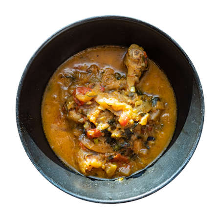 top view of Chakhokhbili (traditional georgian dish from stewed chicken meat, tomato, eggplant and fresh herbs) in black bowl cutout on white background