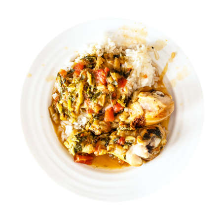 top view of portion of Chakhokhbili (traditional georgian dish from stewed chicken meat, tomato, eggplant and fresh herbs) with boiled rice on white plate cutout on white background