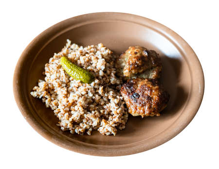 served fried Kotleta (breaded minced beef steaks), side dish from boiled buckwheat porridge on brown plate cut out on white background
