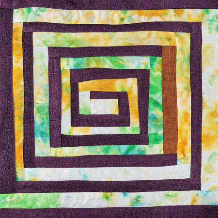 textile background - stitched detail of patchwork fabric with yellow spiral pattern 스톡 콘텐츠