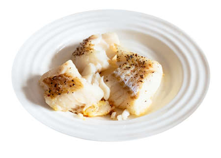 portion of baked and peppered cod fish on white plate cut out on white background 스톡 콘텐츠