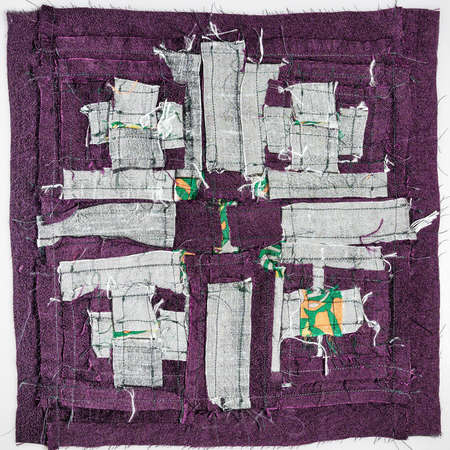 wrong side of stitched detail of patchwork cloth from silver and purple fabrics on white background