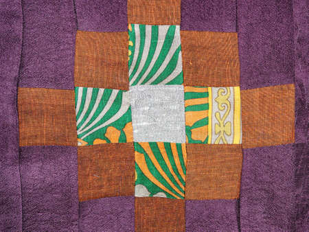 textile background - sewn fragment of patchwork cloth with brown pattern on purple fabric 스톡 콘텐츠