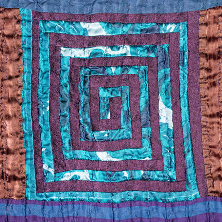 textile background - stitched detail of patchwork fabric with spiral pattern