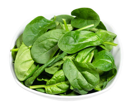 fresh leaves of Spinach leafy vegetable in white bowl cut out on white background