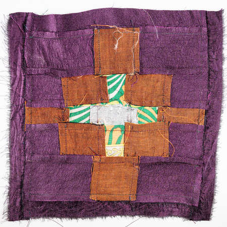 reverse side of stitched detail on patchwork cloth from brown and purple fabrics on white background 스톡 콘텐츠