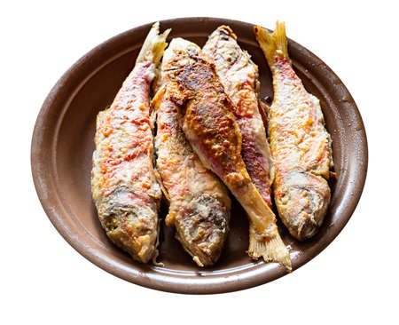 fried red mullet fishes on brown ceramic plate cut out on white background 스톡 콘텐츠