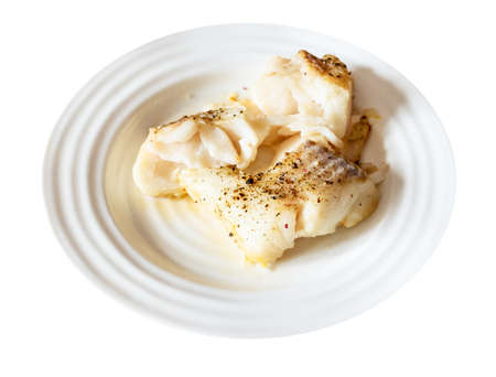 pieces of baked and peppered cod fish on white plate cut out on white background