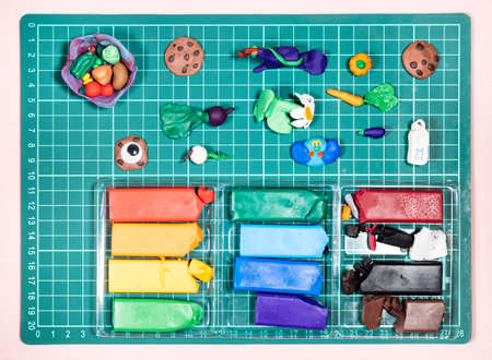 top view of various hand-crafted figurines and colorful polymer clay on green cutting mat on pink paper background 스톡 콘텐츠