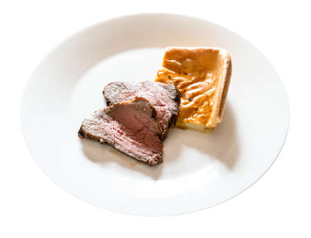 home-made sliced Roast Beef and piece of Yorkshire pudding on white plate cut out on white background