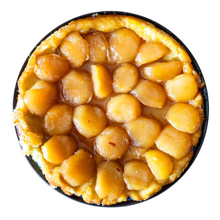 top view of homemade caramelised apple pie Tarte Tatin on plate cut out on white background
