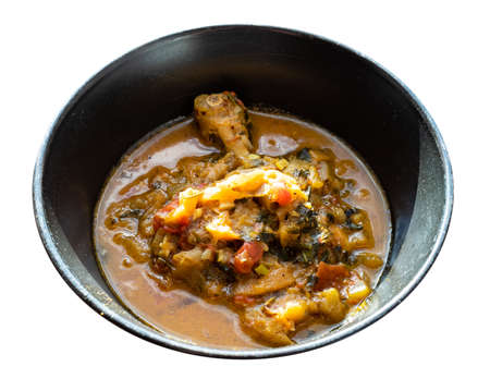 Chakhokhbili (traditional georgian dish from stewed chicken meat, tomato, eggplant and fresh herbs) in black bowl cutout on white background