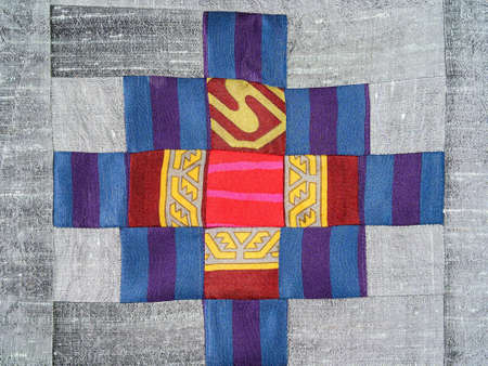 textile background - sewn fragment of patchwork cloth with cross pattern on silver fabric