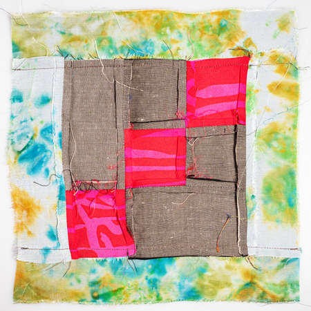 back side of sewn fragment of patchwork cloth from red and brown fabrics on white background