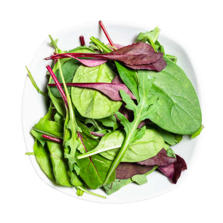 top view of various fresh leaves of leafy vegetables in white bowl cut out on white background 스톡 콘텐츠