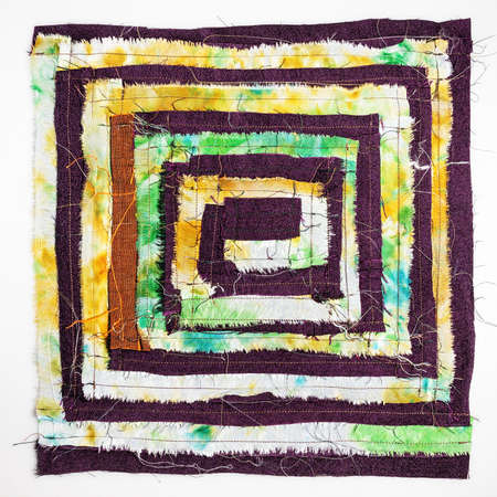 back side of stitched detail of patchwork fabric with yellow spiral pattern on white background