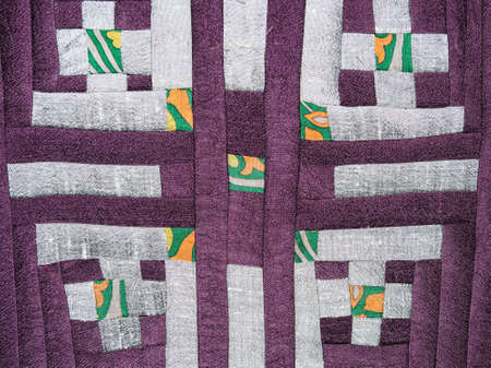 textile background - sewn fragment of patchwork cloth with silver pattern on purple fabrics