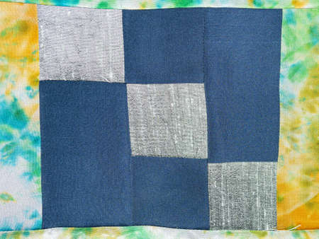 textile background - stitched fragment of patchwork cloth from blue and silver fabrics
