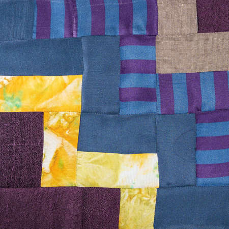 textile background - stitched detail of patchwork cloth from blue and yellow fabrics