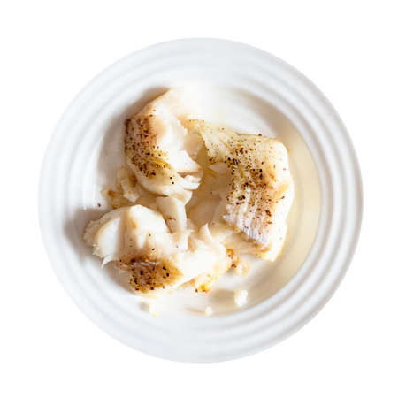 top view of portion of baked and peppered cod fish on white plate cut out on white background