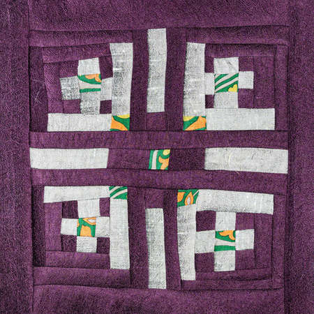 textile background - stitched detail of patchwork cloth with silver pattern on purple fabrics 스톡 콘텐츠