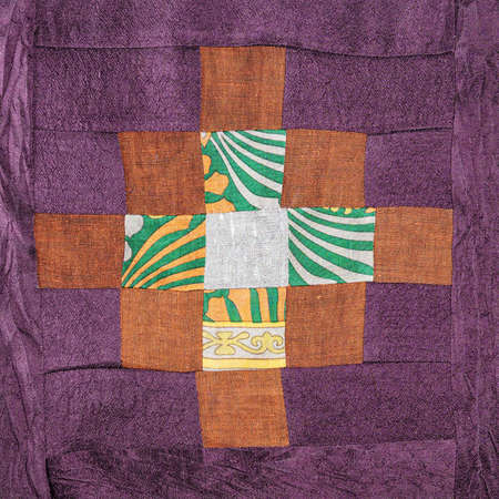 textile background - stitched detail of patchwork cloth with brown cross pattern on purple fabric 스톡 콘텐츠