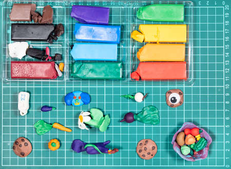 top view of various hand-crafted figurines and colorful polymer clay on green cutting mat