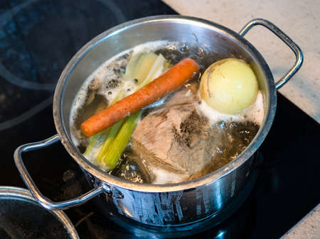 cooking of beef bouillon with vegetables on stove at home kitchen
