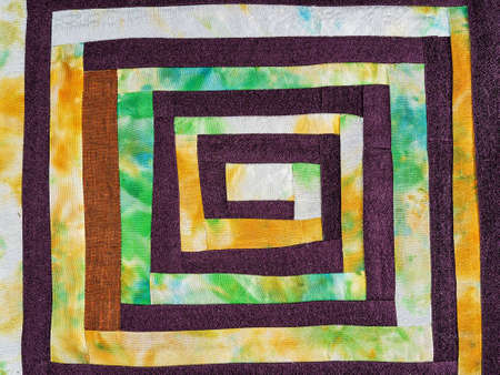 textile background - sewn fragment of patchwork fabric with yellow spiral pattern