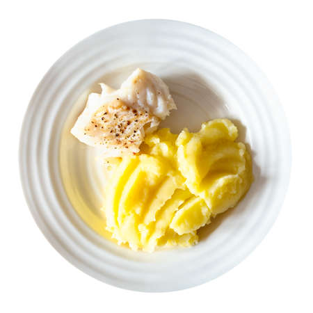 top view of portion of baked and peppered cod fish with mashed potatoes on white plate cut out on white background