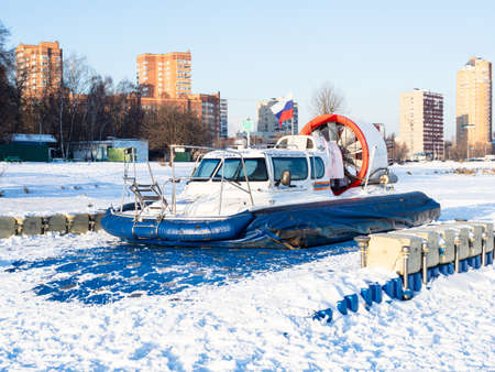 Moscow, Russia - December 12, 2020: rescue boat on pontoon pier on snow-covered frozen Big Sadovy Pond (Academic) pond in Moscow on cold sunny winter day Redakční