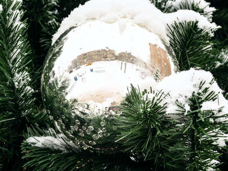 mirrored ball on outdoor Christmas tree close up on overcast winter day Stock fotó