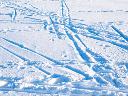 ski tracks in blue snow lit by setting sun in cold winter twiligh