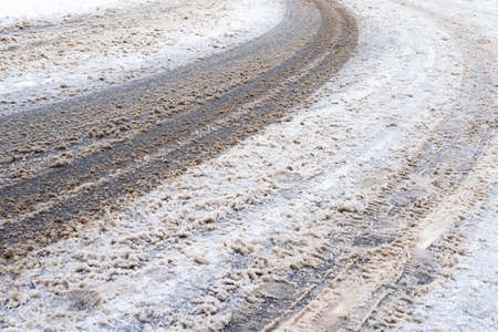 surface of dirty snow-covered slippery road in city on winter day