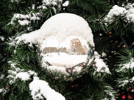 snow-covered mirrored ball on outdoor Christmas tree close up on overcast winter day Stock fotó