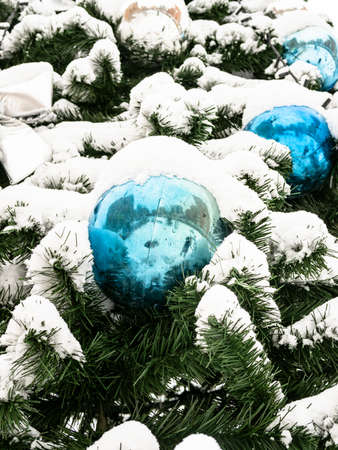 snow-covered ornaments of outdoor decorated Christmas tree close up on overcast winter day