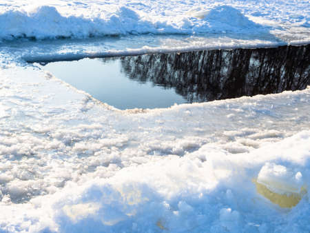 deep ice-hole in frozen snow-covered pond on cold sunny winted day Stock fotó