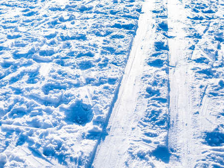 ski track illuminated by sun close up on snow-covered frozen surface of river on cold in cold sunny winter day
