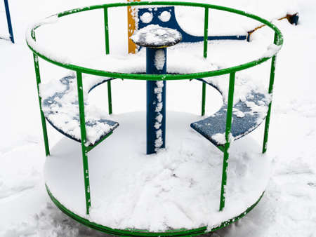 snow-covered outdoor children's roundabout on playground on winter day