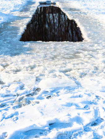 long ice-hole in frozen snow-covered river on cold sunny winted day
