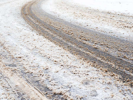 dirty snow-covered slippery road in city on winter day