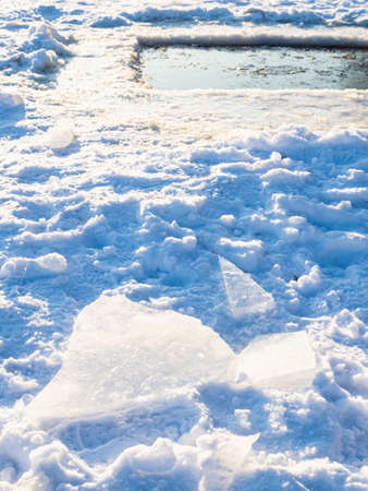 ice blocks on shore of big ice-hole in frozen river on cold sunny winter day (focus on foreground) Stock fotó